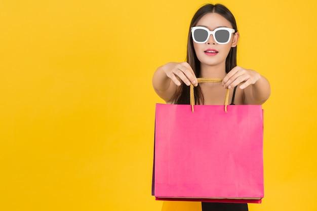 Compras de hermosas mujeres con gafas con bolsas de papel de colores sobre un fondo amarillo.