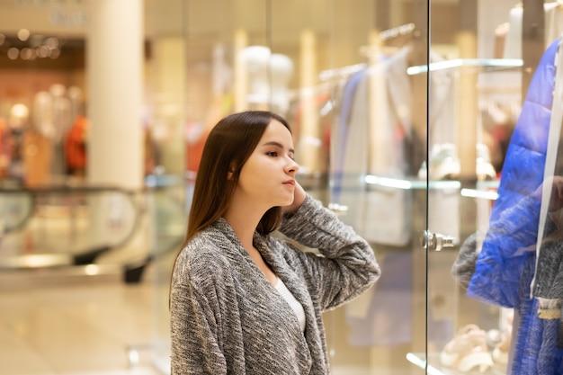 Compras una joven mira los escaparates, sonríe, hace compras en un centro comercial.