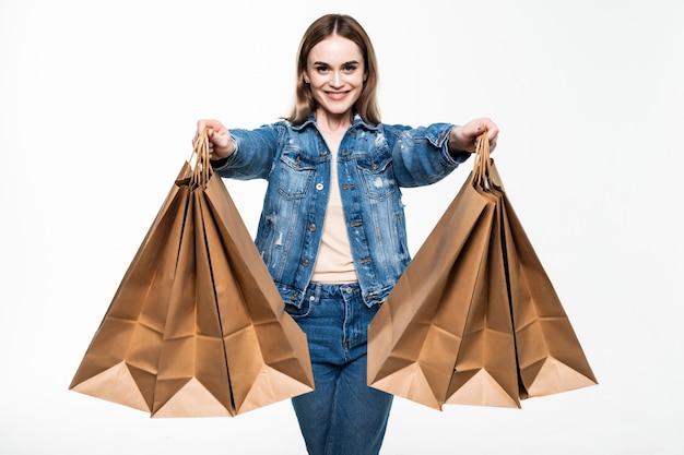 Compras joven sosteniendo bolsas, aisladas en la pared gris del estudio.