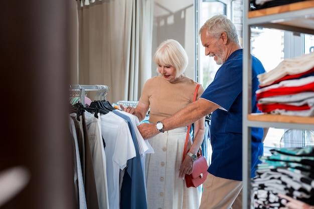 De compras juntos. pareja de ancianos concentrada positiva que elige ropa nueva mientras está de pie cerca de perchas con una colección de moda