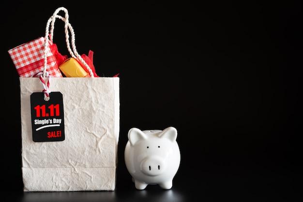 Compras en línea, boleto rojo 11.11 etiqueta de venta de un solo día colgada en una bolsa de compras con caja de regalo