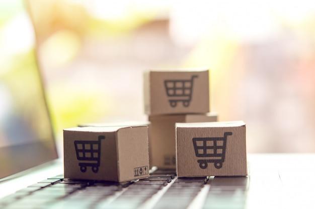 Compras en línea: cajas de cartón o paquetes con el logotipo de un carrito de compras en el teclado de una computadora portátil. servicio de compras en la web en línea y ofrece servicio a domicilio.