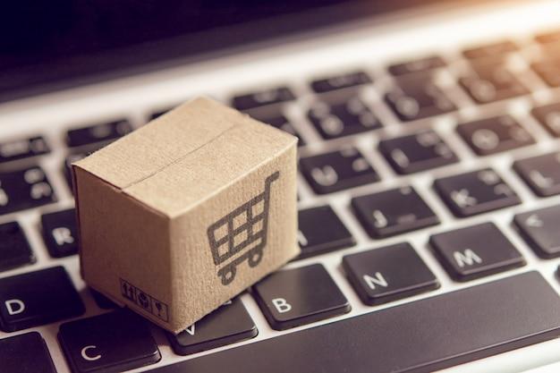 Compras en línea: cajas de cartón o paquetes con el logotipo de un carrito de compras en el teclado de una computadora portátil.