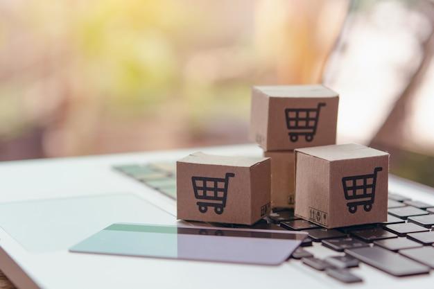 Compras en línea: cajas de papel o paquetes con un logotipo de carrito de compras y una tarjeta de crédito