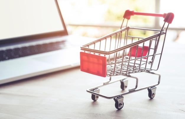 Compras en línea con carrito y computadora portátil.