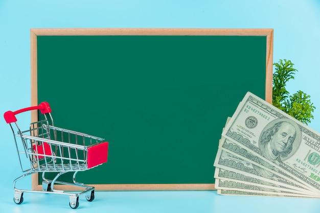 Compras en línea, un carrito doble colocado en un tablero verde sobre un azul.