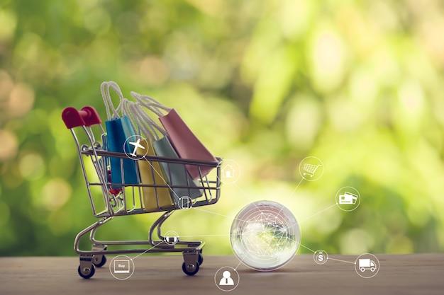 Compras en línea, concepto de comercio electrónico: bolsas de papel en un carrito o carrito de compras con conexión de red de cliente de icono. la compra de productos en internet puede comprar bienes de países extranjeros