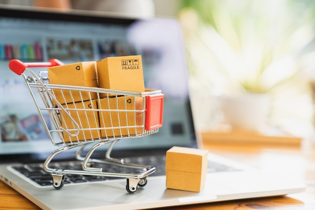 Compras en línea y concepto de entrega, cajas de paquete de producto en carro y laptop