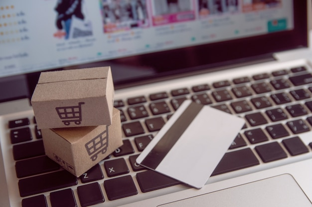 Compras en línea concepto - servicio de compras en la web en línea. con pago con tarjeta de crédito y ofrece servicio a domicilio. paquete o cajas de papel con un logotipo de carrito de compras en un teclado de computadora portátil