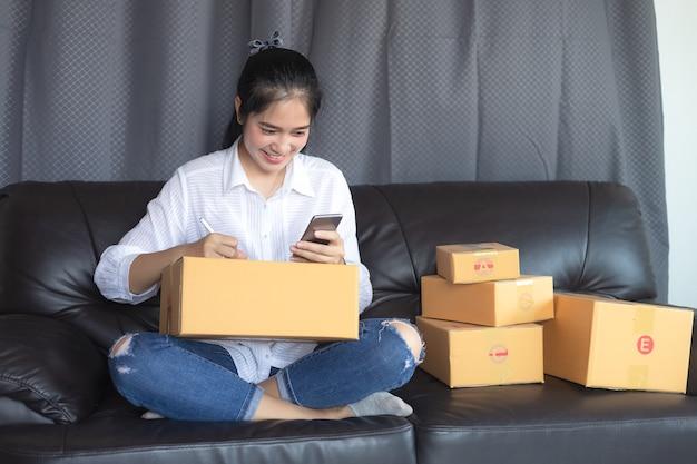 Compras en línea jóvenes comienzan pequeñas empresas en una caja de cartón en el trabajo.