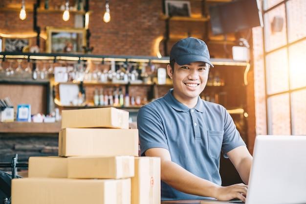 Las compras en línea jóvenes comienzan pequeñas empresas en una caja de cartón en el trabajo.