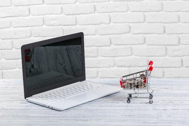 Compras en línea mini carrito de compras y computadora portátil