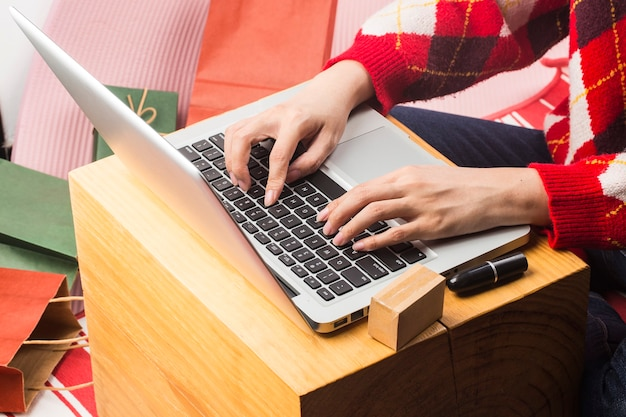 Compras en línea de navidad compradora femenina con portátil se preparan para la víspera de navidad