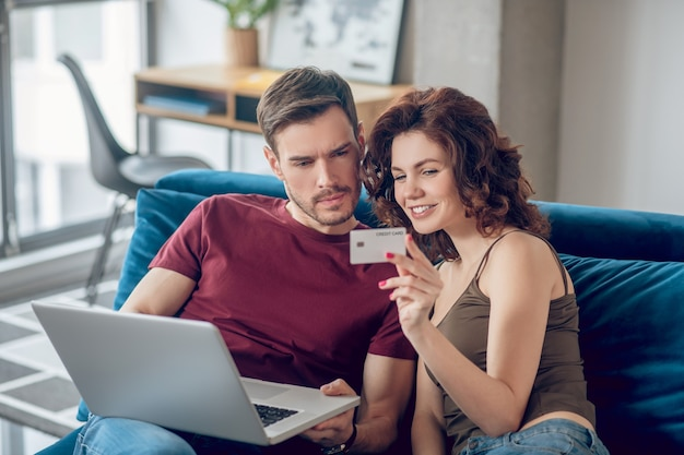 Las compras en línea. pareja joven eligiendo algo para comprar online