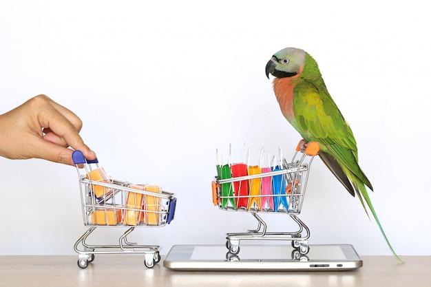 Compras en línea, parrot en modelo de carrito de compras en miniatura y bolso de compras en tableta dispositivo inteligente