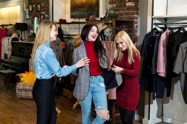 Compras, moda y amistad: tres amigos sonrientes se prueban ropa, una chaqueta en un centro comercial.