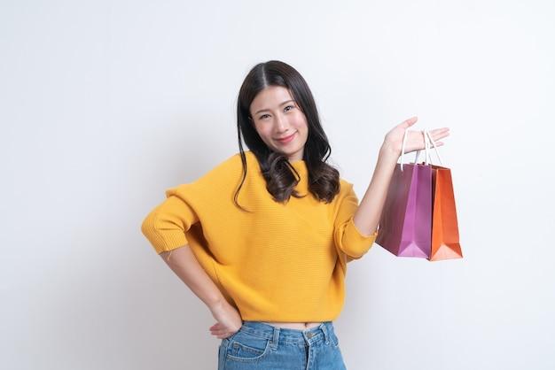 Compras mujer asiática sosteniendo bolsas de compras en camisa yellor con sonrisa feliz en la pared blanca