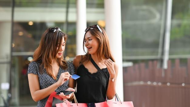 Compras mujer hablando juntos con tarjeta de crédito en el centro comercial.
