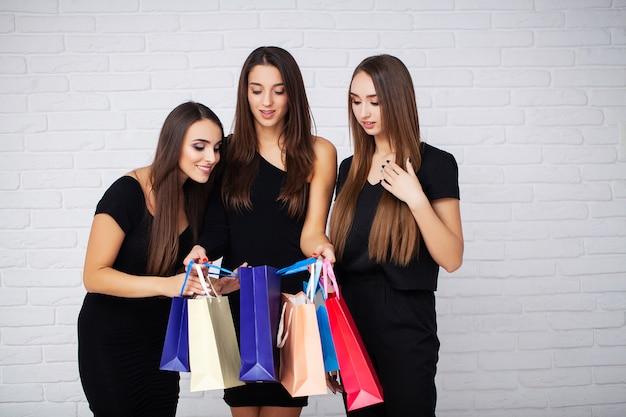 Compras. la mujer morena elegante viste un vestido negro con bolsas de compras, concepto de viernes negro