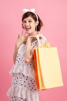 Compras mujer sosteniendo bolsas de compras en rosa