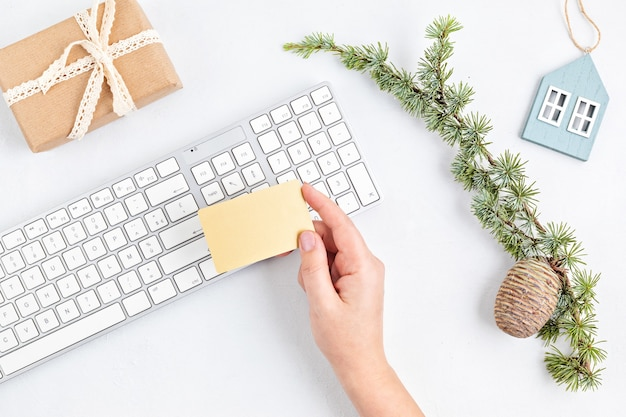 Compras navideñas en línea con cajas de regalo, teclado y maqueta de tarjeta de crédito dorada