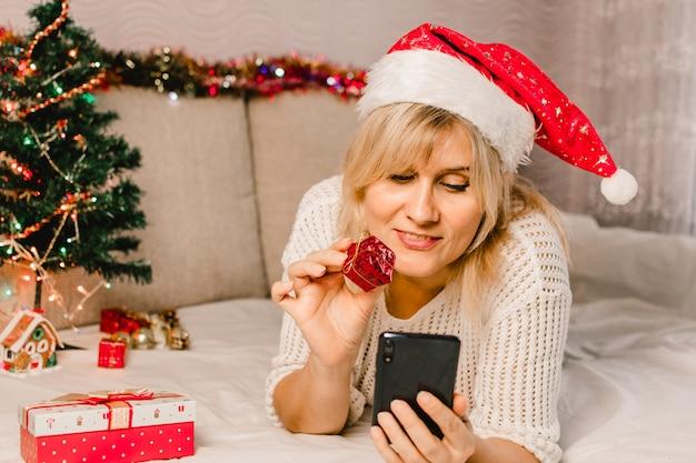 Compras navideñas online. compradora femenina hace un pedido en el teléfono móvil. mujer comprar regalos, prepararse para navidad, caja de regalo en mano. rebajas de vacaciones de invierno.