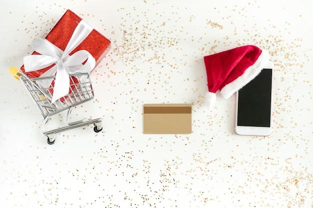 Compras navideñas online. mini carro de compras, celular, tarjeta de crédito y caja de regalo, vista superior