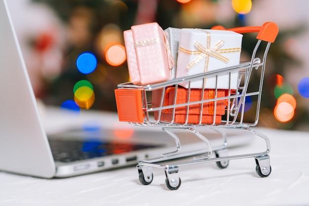 Compras navideñas online. mujer comprar regalos, prepararse para navidad, entre carrito de compras y caja de regalos