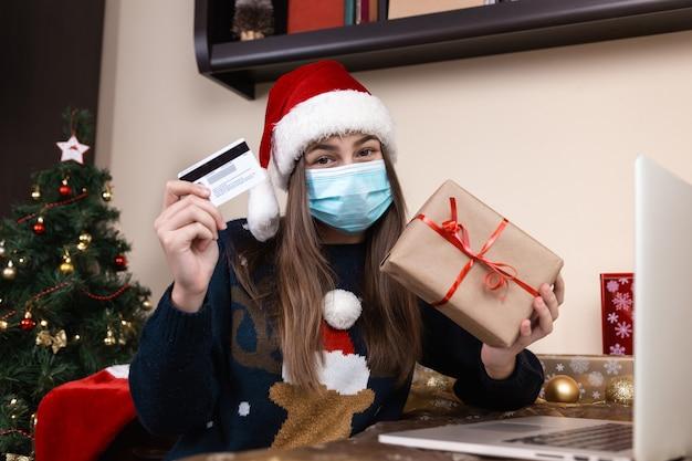 Compras navideñas online. una niña con un sombrero de santa claus y un suéter azul con una máscara médica se sienta cerca de una computadora portátil. la habitación está decorada de forma festiva. navidad durante el coronavirus