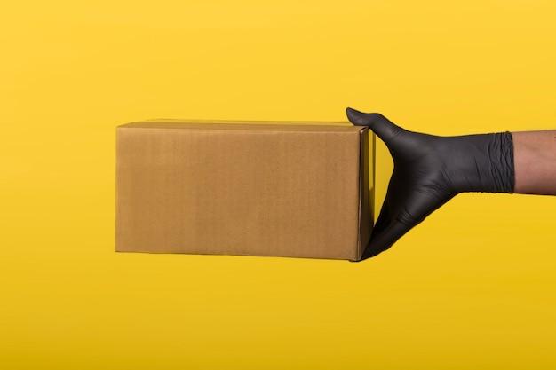 Compras online y entrega urgente. mano de mensajero en guantes de goma médicos con caja marrón aislada sobre fondo de color con espacio de copia. entrega rápida y gratuita en vehículo. primer plano de cuarentena.