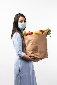 Compras en la pandemia - bastante joven india con máscara protectora mientras sostiene una bolsa de papel con verduras y frutas durante la epidemia del virus