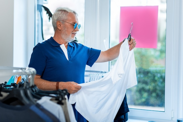 Compras. perfil del elegante hombre de pelo gris positivo de pie en la tienda mientras elige una nueva camiseta blanca con curiosidad