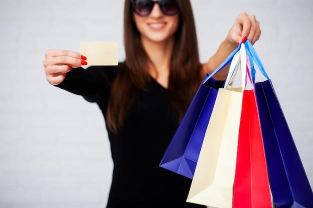 Compras. primer plano de mujer con bolsa de papel de color sobre fondo de pared blanca
