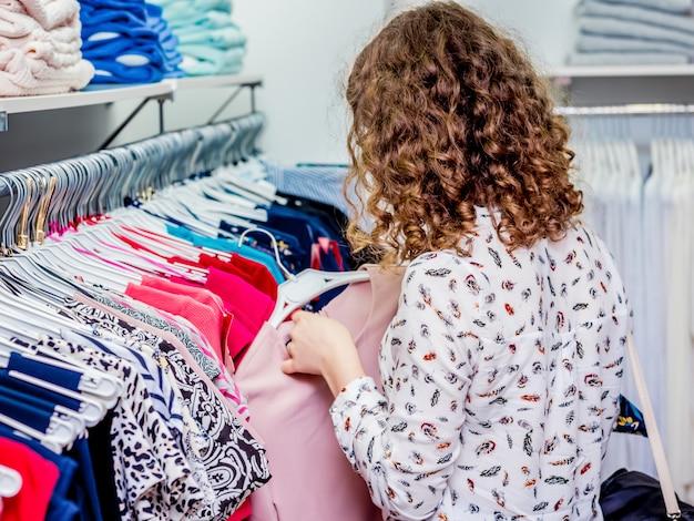 Compras en la tienda de moda. la niña elige ropa en una boutique de moda.