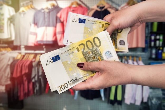 Compras en tienda de ropa, dinero en manos femeninas