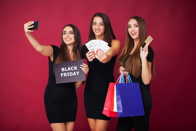Compras. tres mujeres con descuento en blanco en rojo en vacaciones de viernes negro