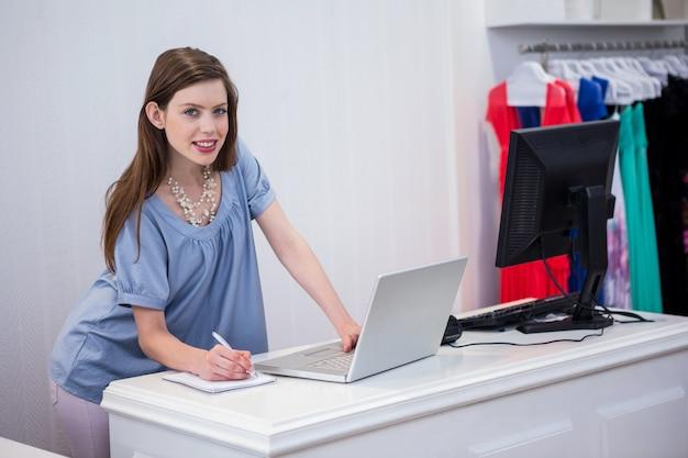 Compre trabajador usando una computadora portátil por la caja