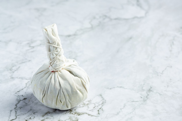 Compresa de hierbas puesta sobre suelo de mármol blanco