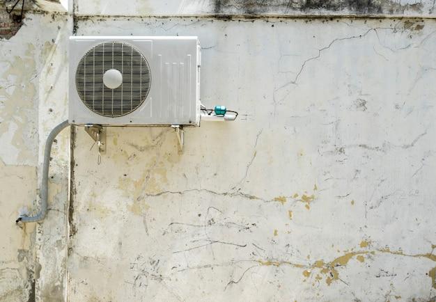Compresor de aire acondicionado instalado en edificio de pared blanca.