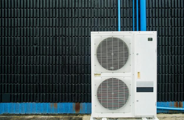 Compresor de aire acondicionado instalado en edificio de pared negro