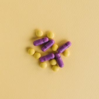 Comprimidos amarillos y cápsulas de color púrpura sobre fondo de textura