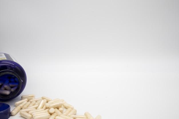 Comprimidos blancos de un frasco de pastillas azul
