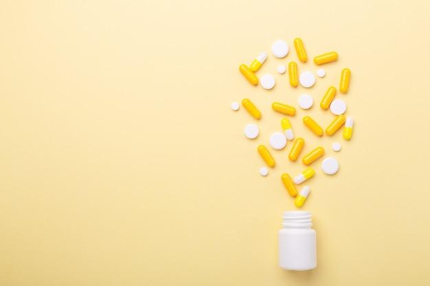 Comprimidos multicolores y pastillas cápsulas de botella de plástico en amarillo