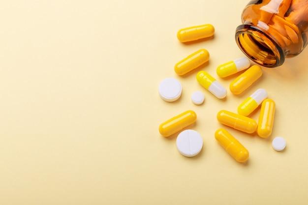 Comprimidos multicolores y píldoras cápsulas de botella de vidrio en amarillo