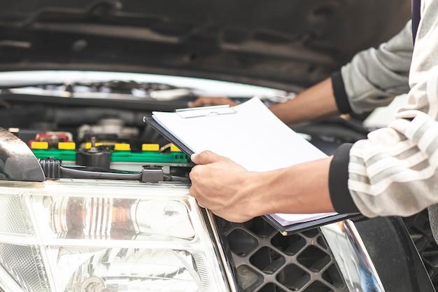 Comprobación mecánica del motor del coche con cheque escrito en el portapapeles de lista de verificación