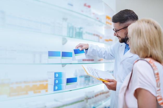 Comprobación de prescripción. hombre guapo morena con uniforme mientras trabajaba en la farmacia