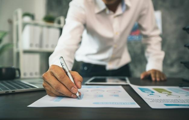 Comprobaciones de hombre de negocios y planificación en gráfico financiero sobre la mesa en la oficina