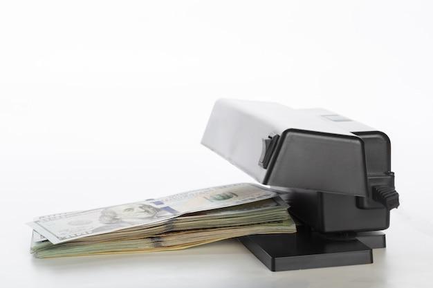 Comprobador de dinero aislado en blanco