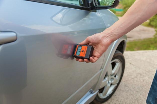 Comprobando la carrocería y las puertas del automóvil, el hombre mide la carrocería del automóvil con el aparato, control de calidad de la pintura del automóvil