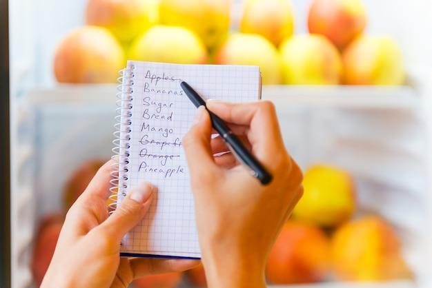 Comprobando lista de compras. close-up de mujer comprobando la lista de compras con manzanas en el fondo